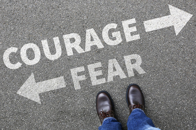 Looking down at the street, a man's shoes are there and the words courage with an arrow right, and fear with an arrow left are before the man's legs and feet.