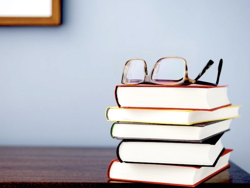 Stack of books on a table with reading glasses on top